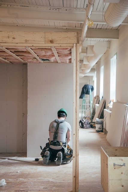man kneeling and remodeling a house